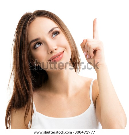 smiling looking up young woman in casual smart clothing, showing something or copyspace for text or slogan, or making idea gesture, isolated against white background - stock photo