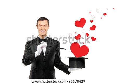 Smiling magician and a red heart shaped objects coming out of a top hat isolated on white background - stock photo