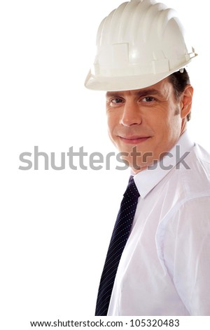 Smiling male architect wearing hard hat and smiling at camera - stock photo
