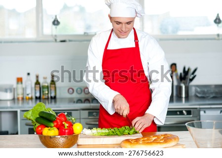 Smiling male chef cutting vegetables on cutting board - stock photo