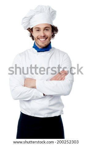 Smiling male chef in white uniform with crossed arms - stock photo