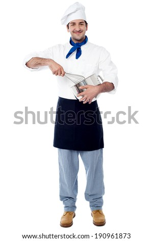 Smiling male chef mixing ingredients in a bowl - stock photo