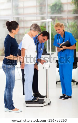 smiling male doctor measuring patient's height and weight on scale - stock photo