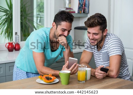 Smiling male friends using phone while standing at table - stock photo