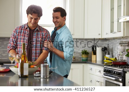 Smiling male gay couple preparing a meal at home look down - stock photo