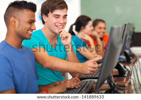 smiling male high school student helping classmate with computer in class - stock photo