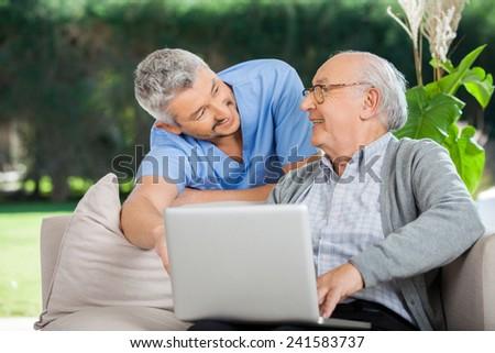 Smiling male nurse assisting senior man in using laptop at nursing home porch - stock photo