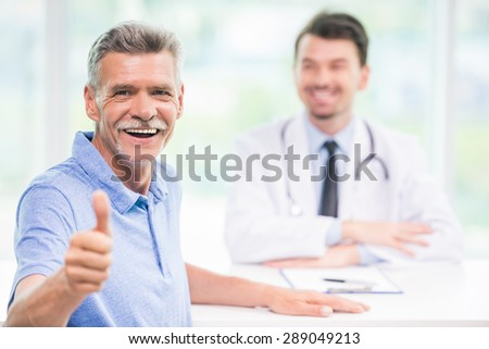 Smiling male patient sitting at doctor's office and looking at camera. - stock photo