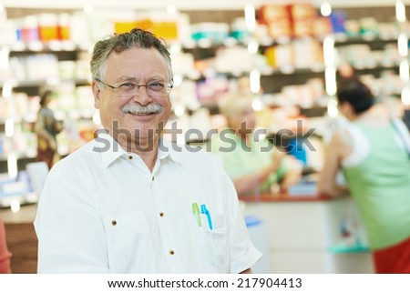 smiling male pharmacist chemist man portrait in pharmacy drugstore - stock photo
