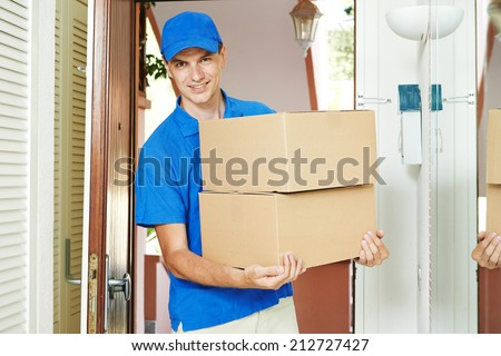 Smiling male postal delivery courier man indoors delivering parcel package boxes - stock photo