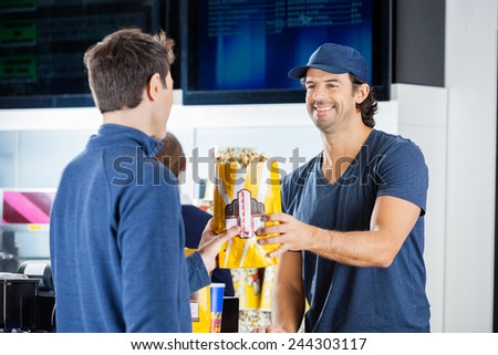 Smiling male seller giving popcorn paperbag to man at cinema concession stand - stock photo