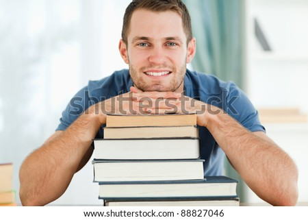Smiling male student leaning on his books - stock photo