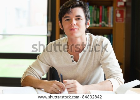 Smiling male student writing an essay in a library - stock photo