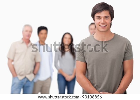 Smiling male with friends behind him against a white background - stock photo