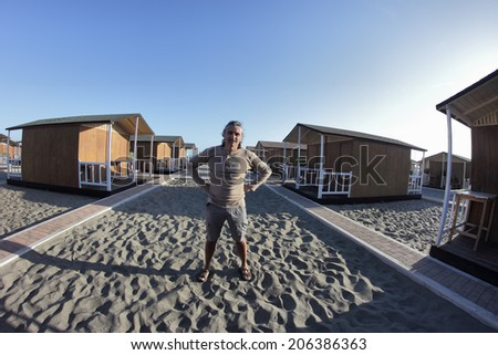 smiling man and beach huts in a fish-eye view - stock photo
