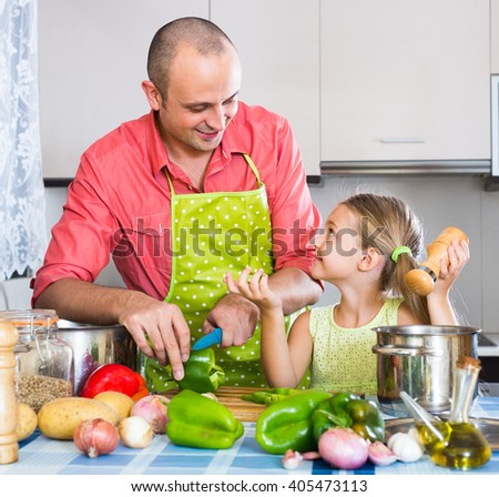 Smiling man and cute little girl cooking together in the kitchen at home