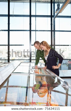 Smiling man and woman looking at a display in a grocery store - stock photo