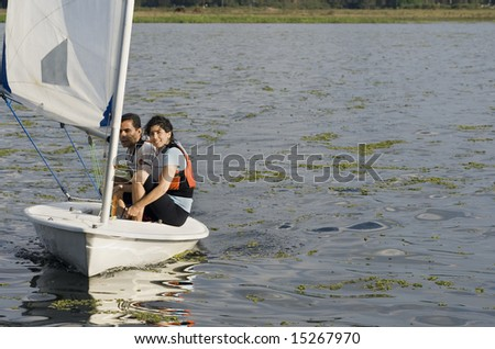 Smiling man and woman sitting on sailboat sailing across lake. Horizontally framed photo - stock photo