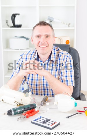 Smiling man at home appliance service workshop - stock photo