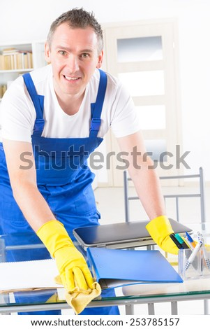 Smiling man cleaner wearing yellow gloves and cleaning office table - stock photo