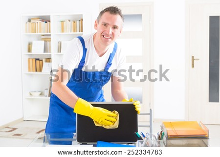 Smiling man cleaner wiping laptop at the office - stock photo