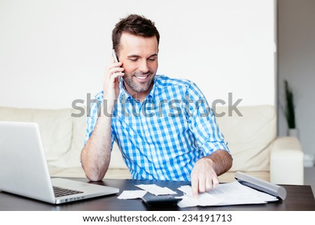 Smiling man discussing some invoices on the mobile - stock photo