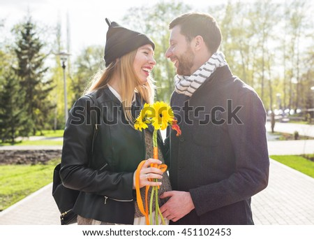 Smiling man embracing happy pregnant woman in a park - stock photo