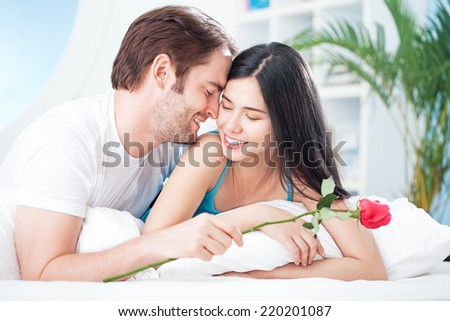 Smiling man giving a rose to his girlfriend on Valentine's Day morning. - stock photo