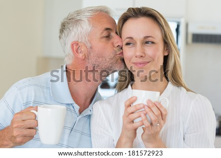 Smiling man giving his partner a kiss on the cheek at home in the kitchen - stock photo