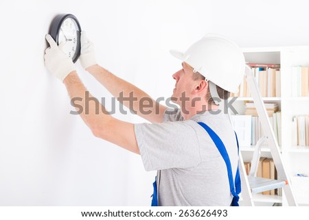 Smiling man hanging wall clock wearing protective helmet - stock photo