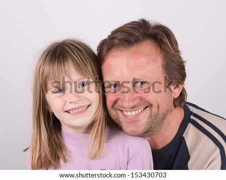 Smiling man holding his daughter in his arms - stock photo