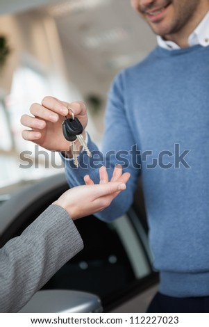Smiling man holding keys in a car shop - stock photo