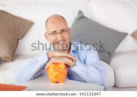 Smiling man holding piggybank at the living room - stock photo