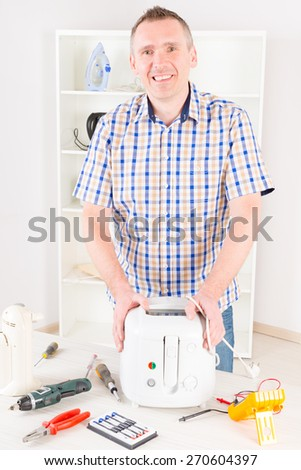 Smiling man holding repaired deep fryer at home appliance service workshop - stock photo