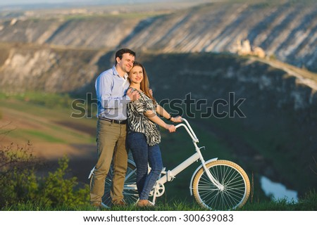 smiling man hugging his girlfriend with bicycle - stock photo
