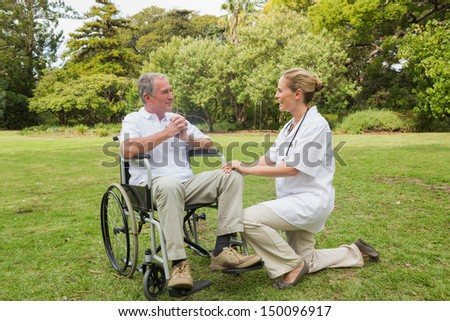 Smiling man in a wheelchair talking with his nurse kneeling beside him in the park on sunny day - stock photo