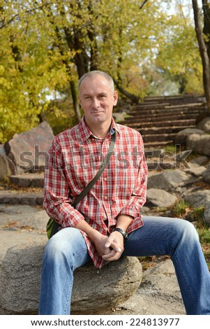Smiling man in autumn park - stock photo