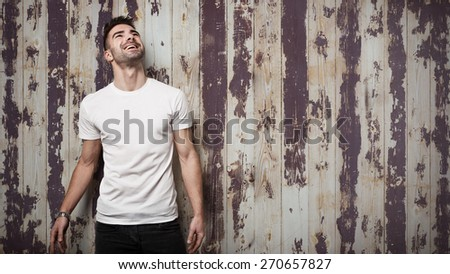 Smiling man in blank t-shirt, grunge wooden wall background - stock photo