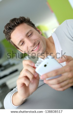 Smiling man in couch using telephone - stock photo