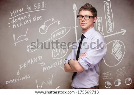 smiling man in glasses near blackboard with economic graphs - stock photo