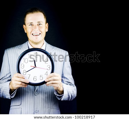Smiling man in gray suit holding a clock on black background with copy space - stock photo