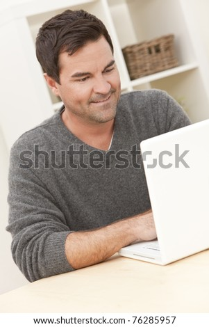 Smiling man in his thirties at home using his laptop computer - stock photo