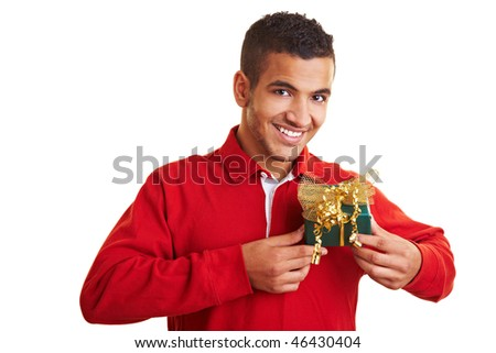 Smiling man in red sweater holding a small gift - stock photo