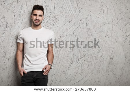 Smiling man in white blank t-shirt, and OSB wooden wall background - stock photo