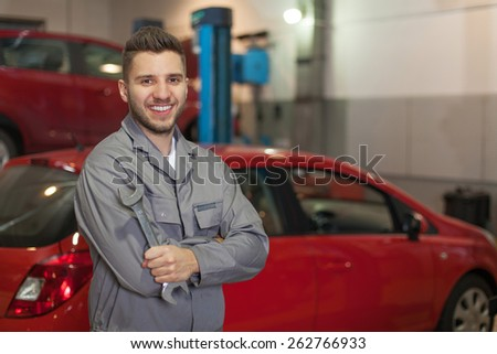 Smiling man in workwear posing with a wrench against two red cars in workshop - stock photo