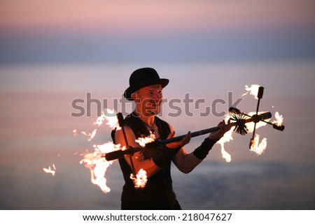 Smiling man juggling with fire torch - stock photo