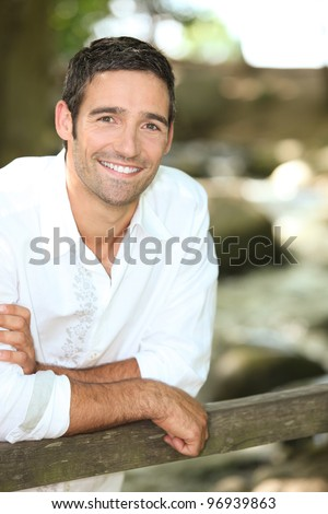 Smiling man leaning on a country gate - stock photo