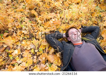 smiling man lying on autumn leaves - stock photo