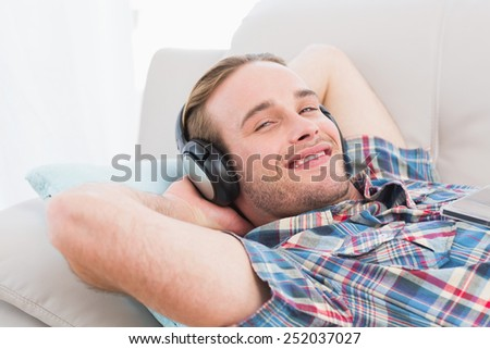Smiling man lying on sofa listening music at home in the living room - stock photo