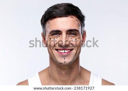 Smiling man marked with lines for plastic surgery - stock photo